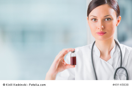 Portrait of pretty female laboratory assistant analyzing a blood