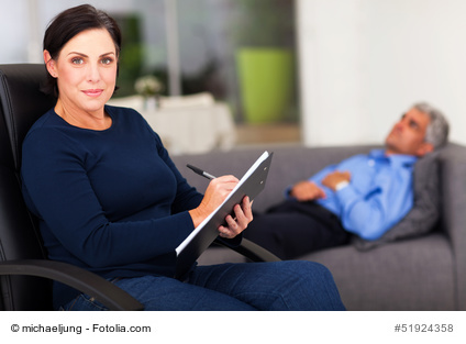 portrait of middle aged female therapist in office with patient in background