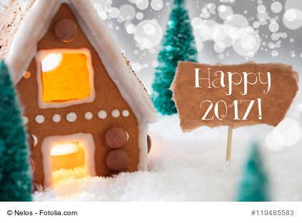 Gingerbread House In Snowy Scenery As Christmas Decoration. Christmas Trees And Candlelight For Romantic Atmosphere. Silver Background With Bokeh Effect. English Text Happy 2017 For Happy New Year