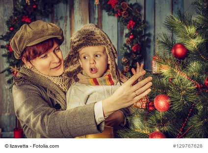 Mother and son decorating a Christmas tree.