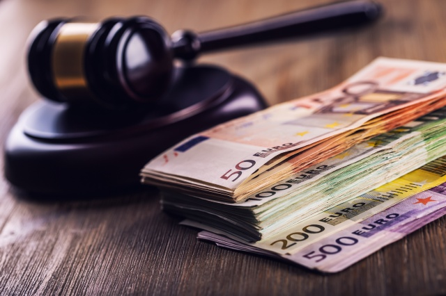 Justice and euro money. Euro currency. Court gavel and rolled Euro banknotes. Representation of corruption and bribery in the judiciary.